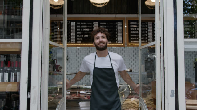 Happy young man opening for service at the butcher's shops looking away daydreaming