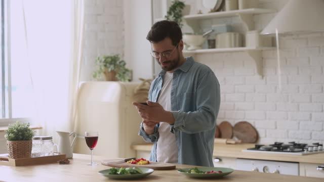 lycklig ung man förbereder romantisk middag med hjälp av smartphone-mobilappar - lunch bildbanksvideor och videomaterial från bakom kulisserna