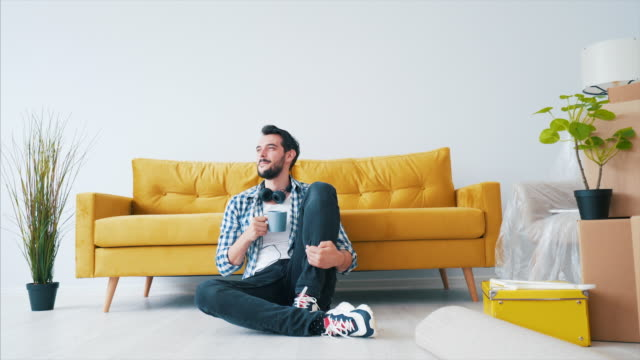 Happy young man relaxing in his new home. Young man sitting on the floor and enjoying a cup of coffee. He just moved in a new house and he is very excited about his place. furniture stock videos & royalty-free footage