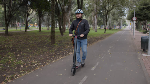 happy young man riding an electric push scooter while enjoying the view - monopattino elettrico video stock e b–roll