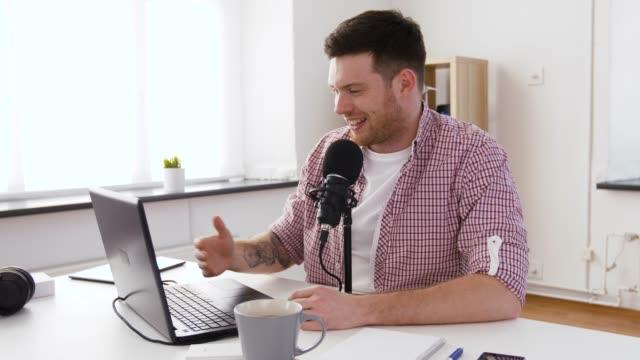 vidéos et rushes de jeune homme heureux avec l'ordinateur portatif et le microphone à la maison - podcasting