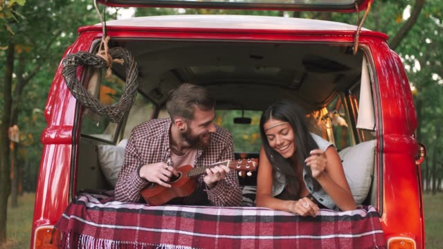 happy young mixed race couple playing instruments and having some fun in retro hippie minibus in forest, slow motion - hippy video stock e b–roll