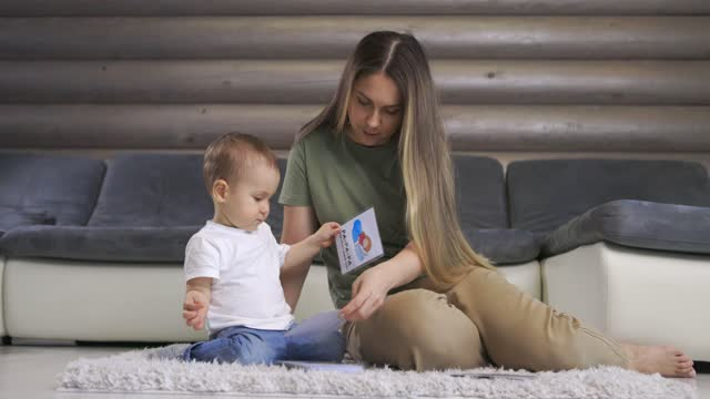 Happy young mother and baby son playing with alphabet card on warm floor at home, early education at home.