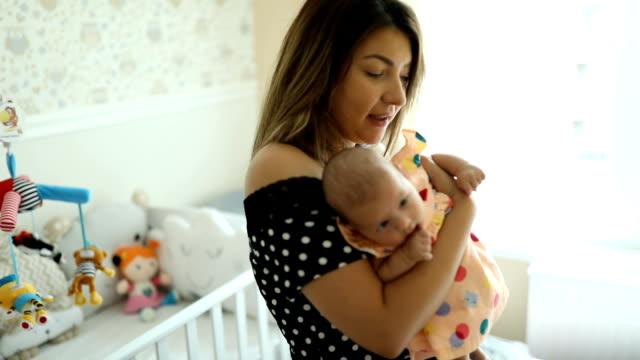 happy young mother holding and singing to her newborn baby - abbigliamento da neonato video stock e b–roll