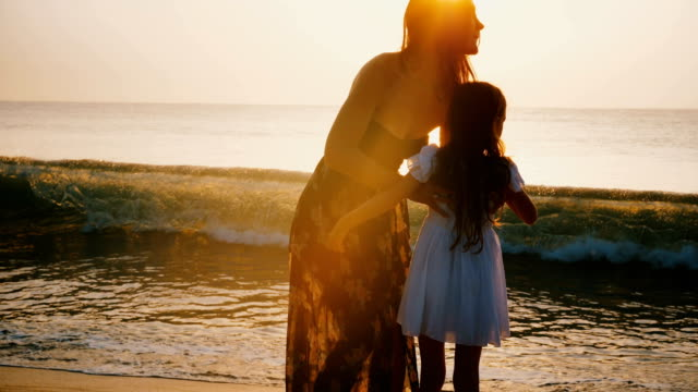vídeos de stock e filmes b-roll de happy young mother holding and spinning little daughter smiling at epic golden sunset beach, concept of family travel. - sri lanka