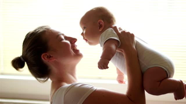 幸せな若い母は、彼女の赤ちゃんを取得します。1 歳 3 か月子、年まで赤ちゃんの世話。母の日 - 母の日点の映像素材/bロール