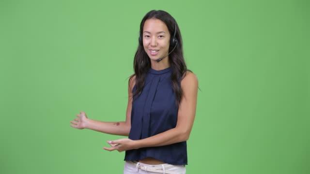 コールセンターの代表者として何かを提示する若い多民族ビジネスウーマンを幸せに - 身ぶり点の映像素材/bロール