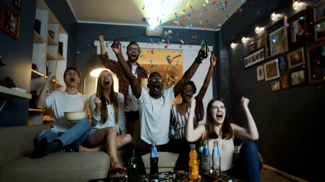 Video Happy young multiethnic fans raise hands and shout watching sports game at home on TV with projector slow motion.