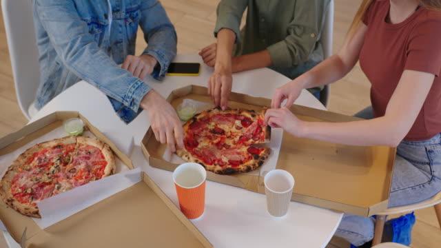 glad ung multietnisk grupp vänner sitter vid bordet hemma och tar bitar av pizza på nära håll - wine box bildbanksvideor och videomaterial från bakom kulisserna