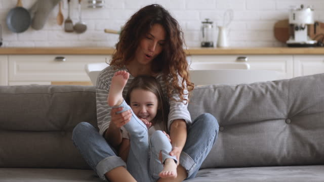 felice giovane mamma che gioca con la figlia carina sul divano - fare il solletico video stock e b–roll