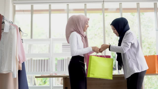 Happy young muslim woman showing  colorful paper shopping bags.