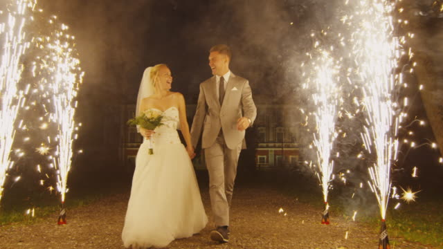 Happy young newlyweds are walking through fireworks in a park in the evening.