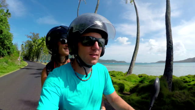 SELFIE: Happy young newlyweds riding Vespa motorbike on Bora Bora honeymoon in sunny summer video