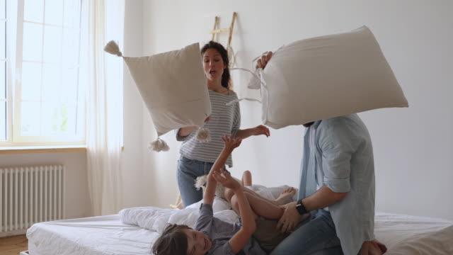 stockvideo's en b-roll-footage met gelukkig jonge ouders verslaan liggend op bed kleine kinderen met kussens. - couple fighting home