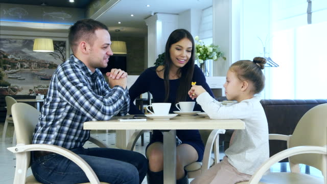 Happy young parents chatting witn daughter during their family vacation in cafe drinking tea video