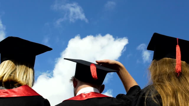 happy young people celebrating graduation, throwing academic hats up in air - tocco accademico video stock e b–roll