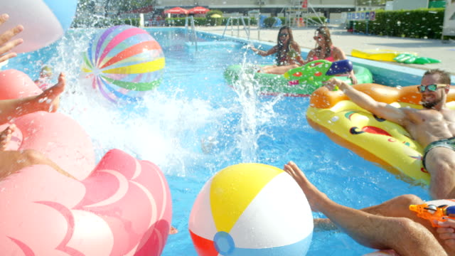 vídeos de stock e filmes b-roll de slow motion: happy young people having fun splashing water on colorful floaties - brinquedos na piscina