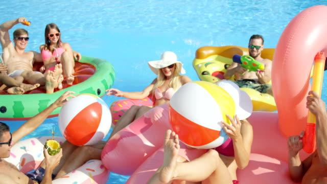 slow motion glücklich junge menschen, die gute zeit auf lustige bunte floaties im pool - spring break stock-videos und b-roll-filmmaterial