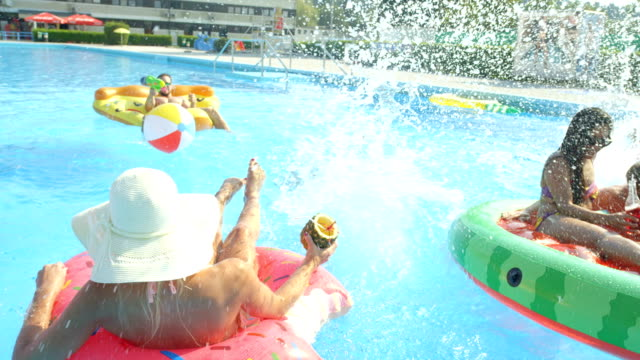 SLOW MOTION CLOSE UP: Happy young people having pool party on sunny summer day SLOW MOTION CLOSE UP Happy smiling students drinking alcohol cocktails on colorful floaties at pool party on spring break. Cheerful young people having fun on inflatable pizza, watermelon and doughnut pool party stock videos & royalty-free footage