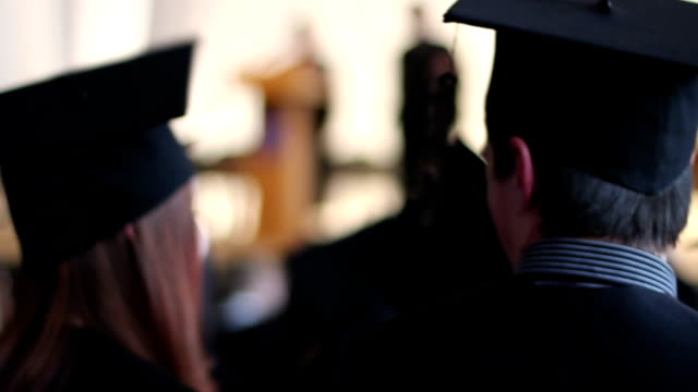 Happy young people in academic caps with tassels talking Happy young people in academic caps with tassels talking at graduation ceremony diploma stock videos & royalty-free footage
