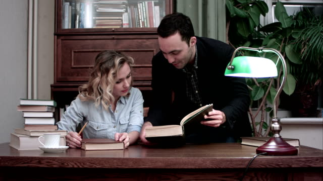 Happy young professor and smiling female student discussing the book for research - vídeo