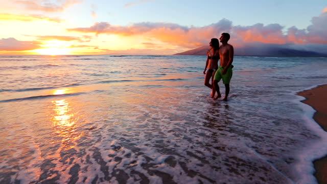 vídeos y material grabado en eventos de stock de feliz pareja romántica caminando en la playa mientras disfruta de la puesta de sol - caribe