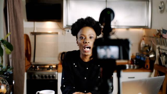 glückliche junge erfolgreiche weibliche schwarze vlogger machen neue video für blog mit professionellen kamera zu hause zeitlupe. - nachhilfelehrer stock-videos und b-roll-filmmaterial