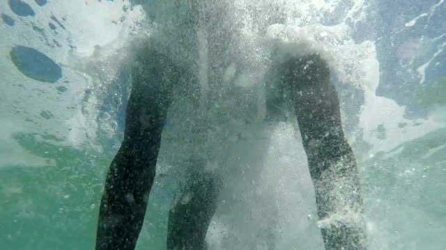 SLOW MOTION CLOSE UP: Happy young surfer doing duck dive video