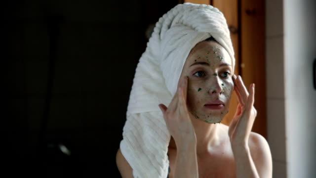 stockvideo's en b-roll-footage met gelukkig jonge vrouw gezichtsmasker in badkamer toe te passen. - mirror mask