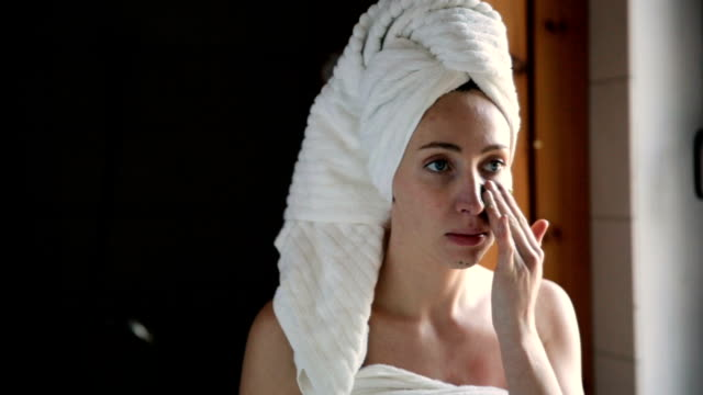 happy young woman applying face mask in bathroom. - skin care stock videos & royalty-free footage