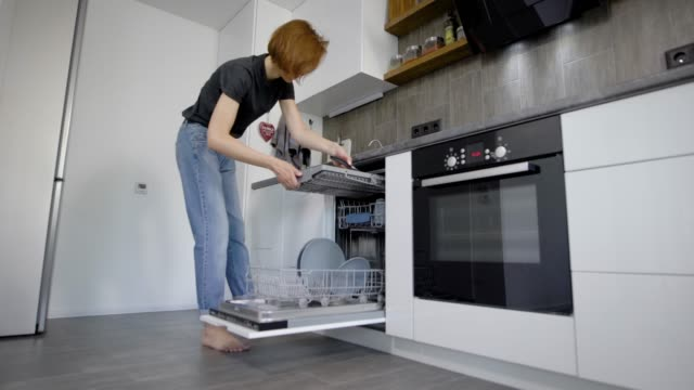 Happy Young Woman Arranging Plates In Dishwasher At Home Happy Young Woman Arranging Plates In Dishwasher At Home. A woman is folding dirty dishes dishwasher stock videos & royalty-free footage