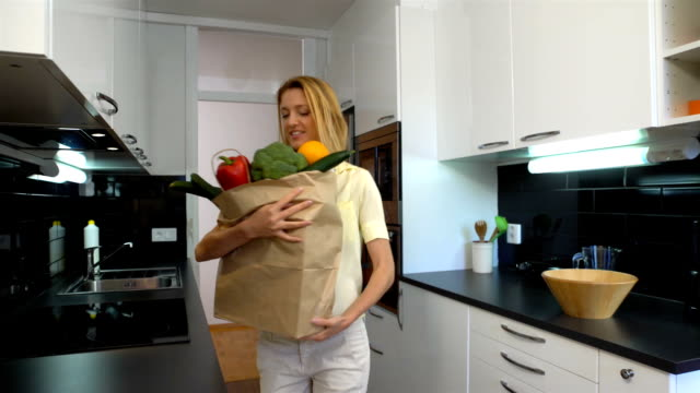 Happy Young Woman Brings A Bag Of Groceries To The Kitchen video