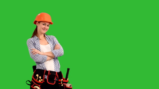 happy young woman builder fun dancing on a green background video