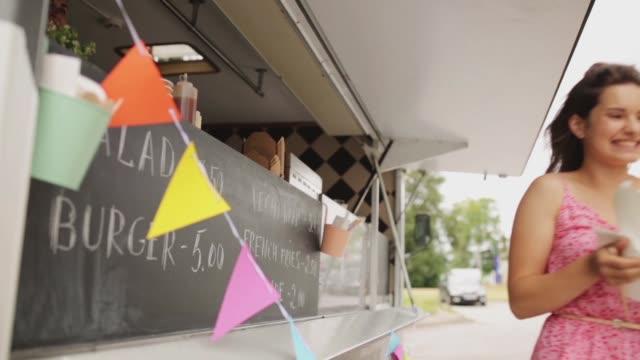 stockvideo's en b-roll-footage met gelukkig jonge vrouw maaltijd op food truck kopen - foodtruck