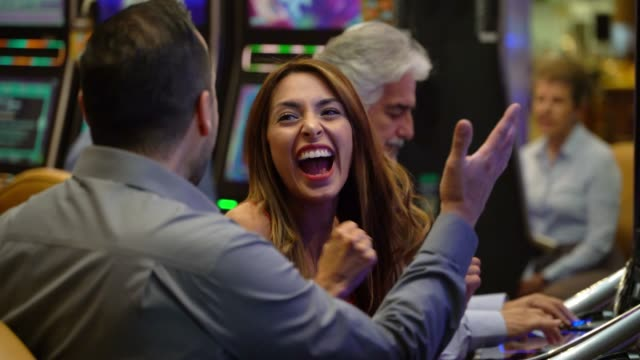 Happy young woman celebrating with the man next to him a win on the slot machines