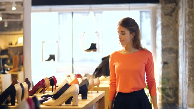 happy young woman choosing shoes at store - scarpe video stock e b–roll