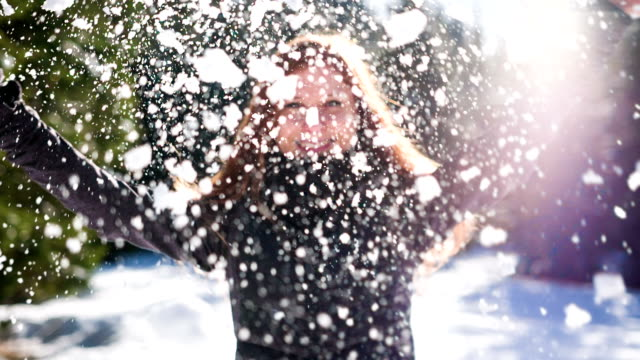 Happy young woman crushing a snowball in the air video