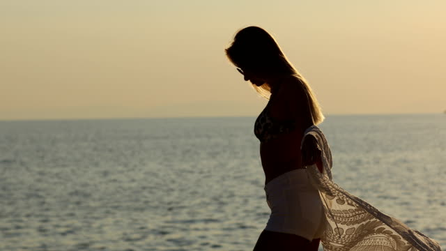 Happy young woman dancing by the sea