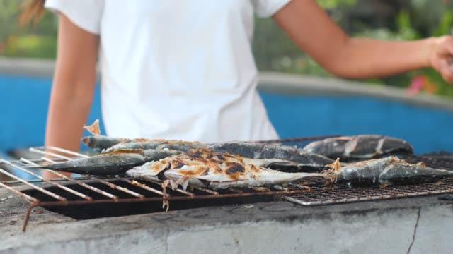 giovane donna felice che balla mentre cucina il pesce alla griglia in giardino in estate. - filippino video stock e b–roll