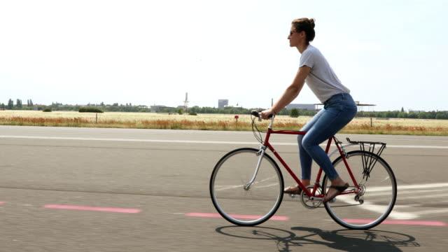 stockvideo's en b-roll-footage met gelukkig jonge vrouw genieten van de vrijheid van fietsen - fiets