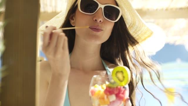 vídeos de stock, filmes e b-roll de mulher nova feliz que tem férias na praia - fruit salad