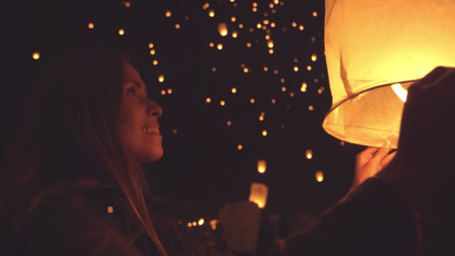 Happy young woman holding lit paper lantern at night during lantern festival Happy young millennial woman holding flaming fire lantern at night during giant lantern festival outside lantern stock videos & royalty-free footage