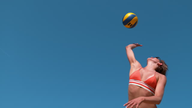 LOW ANGLE: Happy young woman in bikini serving ball during beach volleyball game SLOW MOTION, LOW ANGLE, CLOSE UP: Happy young Caucasian woman in a bikini serving the ball during a beach volleyball game. Athletic female volleyball player jumps into the air and smashes the ball. beach volleyball stock videos & royalty-free footage