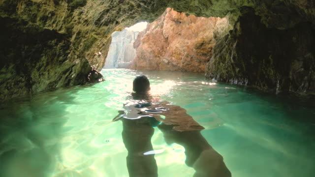 stockvideo's en b-roll-footage met gelukkig jonge vrouw in bikini zwemmen in water grot in de buurt van ponza eiland kust zee in italië - baai
