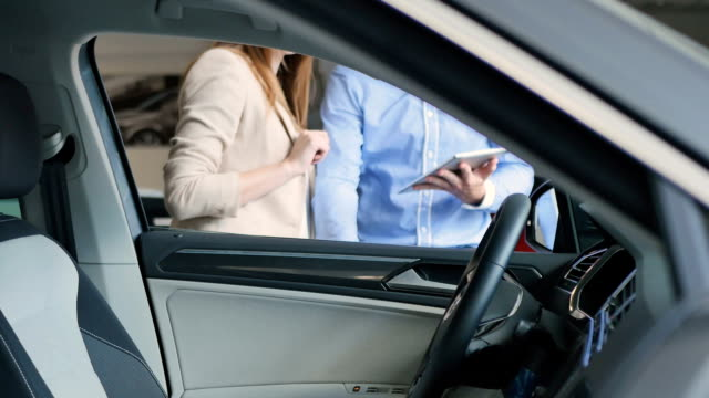Happy young woman inspects the car's interior and show a thumb up to salesman video
