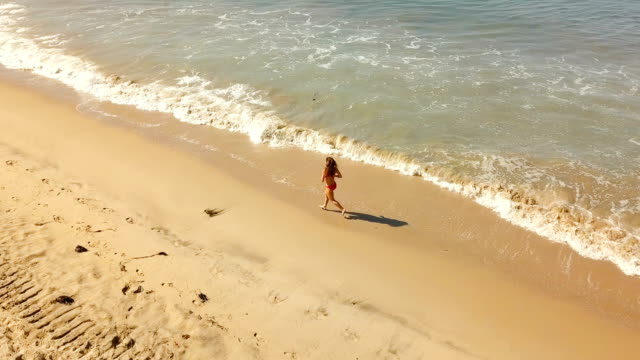 happy young woman jumping and running around at the beach. happy young woman jumping and running around at the beach in california. attraktive frau stock videos & royalty-free footage