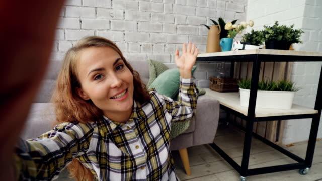 vídeos de stock, filmes e b-roll de mulher jovem feliz olhando para a câmera, segurando o smartphone e falando com amigos on-line, sorrindo e gesticulando parado em casa. conceito de comunicação e pessoas. - blogar