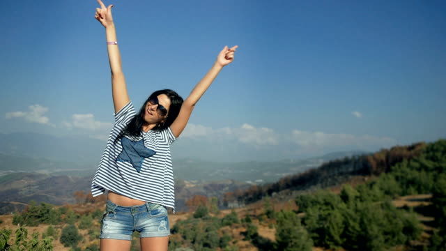 Happy young woman looking at the mountains on the edge of a cliff. video