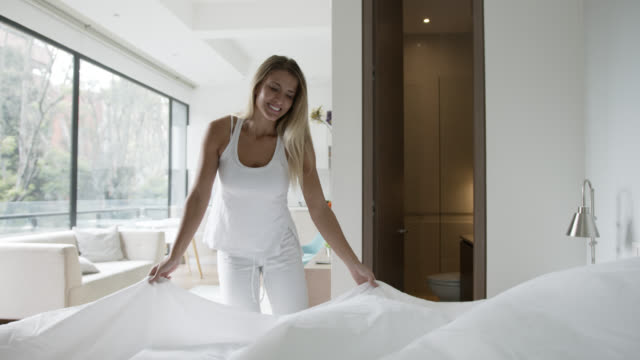 Happy young woman making her bed looking cheerful