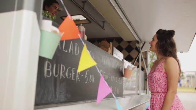 stockvideo's en b-roll-footage met gelukkig jonge vrouw maaltijd bestellen op food truck - foodtruck
